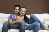 Couple sitting on a couch with arm around — Stock Photo