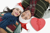 Couple lying on a floor with Christmas present — Stock Photo
