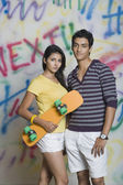 Couple standing with a skateboard — Stock Photo