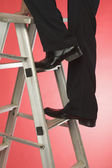 Businessman moving up a step ladder — Stock Photo