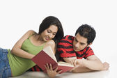 Couple lying on the floor and reading a book — Stock Photo