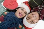 Couple lying on a floor with Christmas present — ストック写真
