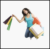 Woman carrying shopping bags and jumping on a trampoline — Stock Photo