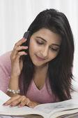 Mujer leyendo un libro mientras hablaba en un teléfono móvil — Foto de Stock