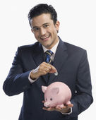 Businessman putting a coin into a piggy bank — Стоковое фото