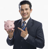 Businessman pointing at a piggy bank — Stock Photo