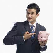Affärsman som pekar på en spargris — Stockfoto