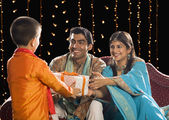 Couple giving Diwali gift to their son — Stock Photo