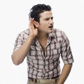 Mann versucht, mit einer hohlen hand an seinem ohr zu hören — Stockfoto