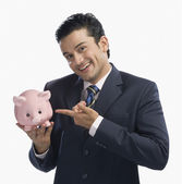 Businessman pointing at a piggy bank — Foto Stock