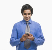 Businessman text messaging on a mobile phone — Stock Photo