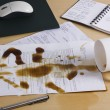 Spilt coffee over documents on a desk — Stock Photo