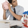 Real estate agent holding a piggy bank — Stock Photo