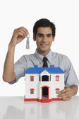Real estate agent holding keys and a model home — Stock Photo