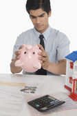 Real estate agent looking into a piggy bank — Stock Photo