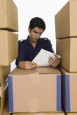 Store manager reading papers with cardboard boxes — Stock Photo