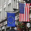 American flag and European Union flag hanging in front of a building — Stockfoto