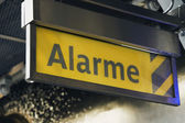 Alarm sign at a railroad station — Stock Photo