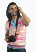 Photographer holding a digital camera and talking on a mobile phone — Stock Photo