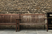 Benches in front of a weathered wall — Stock Photo