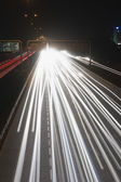 Streaks of headlights of moving vehicles on the road — Stock Photo
