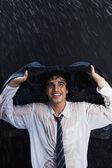 Businessman enjoying in the rain — Stock Photo