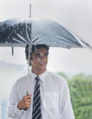 Businessman sheltering under umbrella in rain — Stock Photo