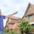 Man and wife and pointing towards a house — Stock Photo #33114675