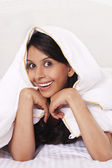 Woman covering herself with a bed sheet — Stock Photo