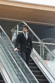 Businessman moving down on an escalator — Stock Photo