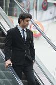 Businessman moving down on an escalator — Stock Photo