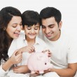 Family with a piggy bank — Stock Photo #33136429