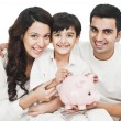 Happy family with a piggy bank — Stock Photo #33137655