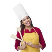 Happy woman holding a spatula and ladle — Stock Photo