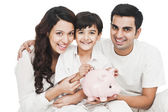 Happy family with a piggy bank — Stock Photo