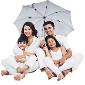 Family sitting under an umbrella — Photo