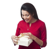 Happy woman opening a gift box — Stock Photo