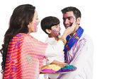 Family celebrating Holi festival — Stock Photo