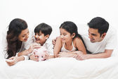 Family with a piggy bank on the bed — Stock Photo