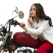 Woman applying lipstick on her lips on a motorcycle — Stock Photo