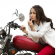 Woman applying lipstick on her lips on a motorcycle — Stock Photo #33275921