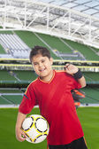 Boy carrying a soccer ball and his shoes — Stock Photo