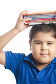 Boy holding a stack of books over his head — Stock Photo