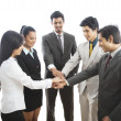 Stock Photo: Business executives stacking their hands and smiling