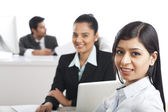 Portrait of two businesswomen smiling in an office — Stock Photo