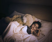 Girl sleeping on the bed with a teddy bear — Stock Photo