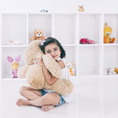 Portrait of a girl holding a teddy bear and smiling — Stock Photo