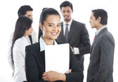 Portrait of a businesswoman smiling with her colleagues in the background — Stock Photo