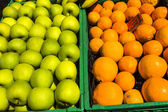 Granny smith apples and oranges in the crates for sale at a mark — Stock Photo
