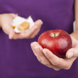 Young woman holding candy and apple — Stock Photo